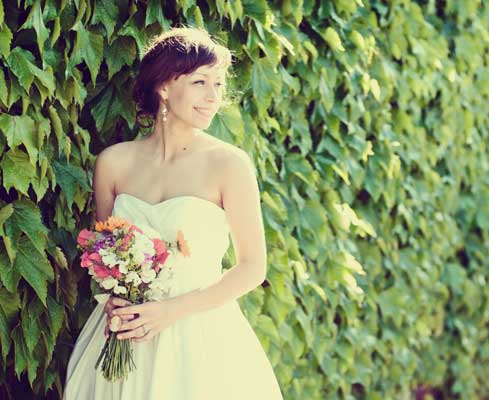 Bride against wall of flowers