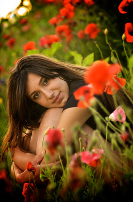 Beautiful girl sitting among the roses